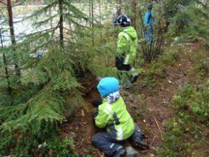 Lapsia leikkimässä metsässä.