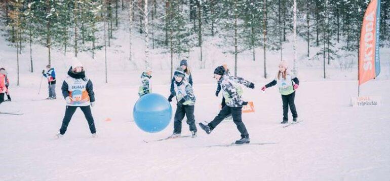 Lapset leikkivät lumisessa maisemassa hiihtäen