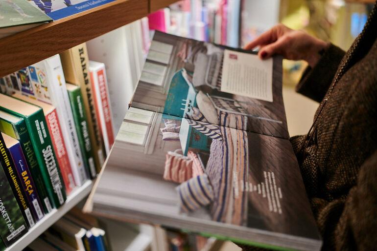 Kirjaa selaillaan kirjahyllyn edessä.